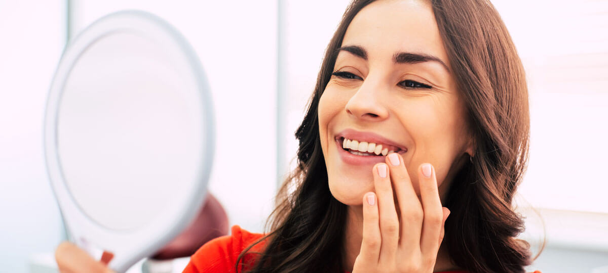 femme contente après la pose d'un implant dentaire